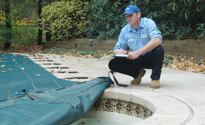 Photo of a Jayson Pool Technician inspecting an in-ground pool