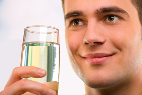 Photo of a man holding up a clean, spot-free glass of water.